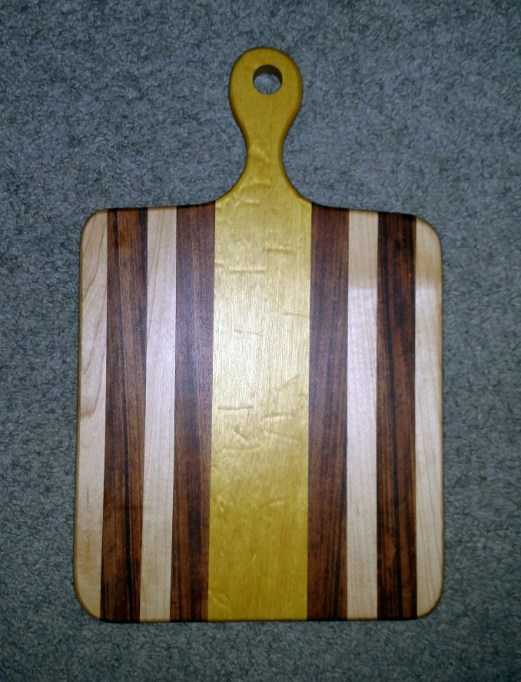 "Small Sous Chef 16 - 022. Hard Maple, Goncalo Alves & Quilted Yellowheart. 9"" x 16"" x 3/4""."