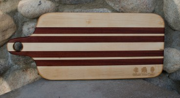 "Engraved 16 - 55. Bread board made for Urban Tree Care. Hard Maple and Bubinga. 8"" x 20"" x 1""."