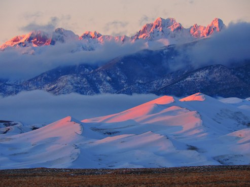 "This picture of Great Sand Dunes National Park & Preserve in Colorado is a perfect combination of stone, sand, snow and light. The Sangre de Cristo (""Blood of Christ"") Mountains were named by early explorers for the crimson light that often appears on them at sunrise or sunset. The red color is especially vivid when the mountains and dunes are covered with snow. Photo by Patrick Myers, National Park Service. Posted on Tumblr by the US Department of the Interior, 2/5/17."