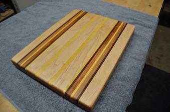 # 63 Cutting Board, $125. Edge grain cutting board. Hard Maple, Black Walnut, Cherry and Yellowheart.