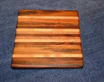 """Cheese Board # 13 - 00. This is the board that started it all ... the first cheese board I ever made, and gave to Velda for Christmas. Board has been resurfaced after 2 years of use, and the rubber feet have been replaced with the upgraded version I started using immediately after making the board. Goncalo Alves, Honey Locust, Jatoba, Black Walnut and Cherry edge grain. 10"""" x 11"""" x 1""""."""