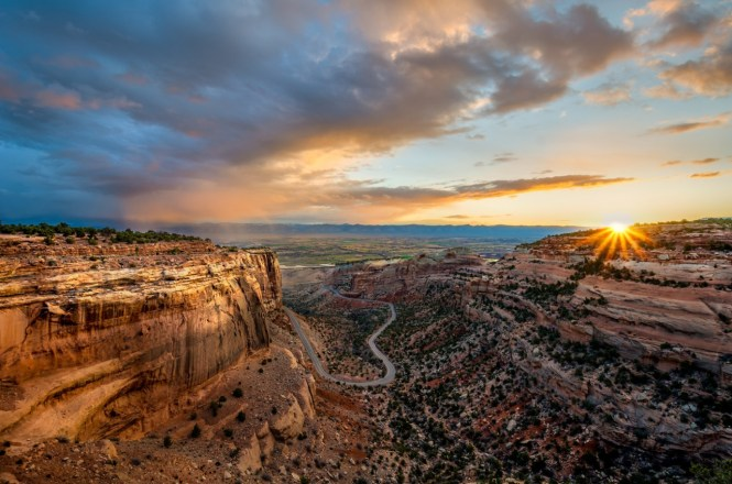 The Colorado National Monument rises more than 2,000 feet above the Grand Valley of the Colorado River. Towering monoliths exist within a vast plateau and canyon panorama. You can experience sheer-walled, red rock canyons along the twists and turns of Rim Rock Drive or hike some of the park's more than 40 miles of maintained trails. Sunrise photo over the monument by William Woodward. Posted on Tumblr by the US Department of the Interior, 4/20/15.