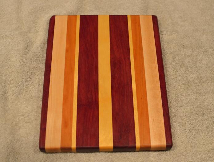 "Cheese Board # 15 - 064. Purpleheart, Hard Maple, Cherry & Yellowheart. 9"" x 11"" x 3/4""."
