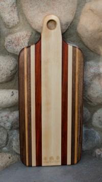 "Engraved 16 - 53. Bread board made for Urban Tree Care. Black Walnut, Cherry, Hard Maple and Jatoba. 8"" x 20"" x 1""."