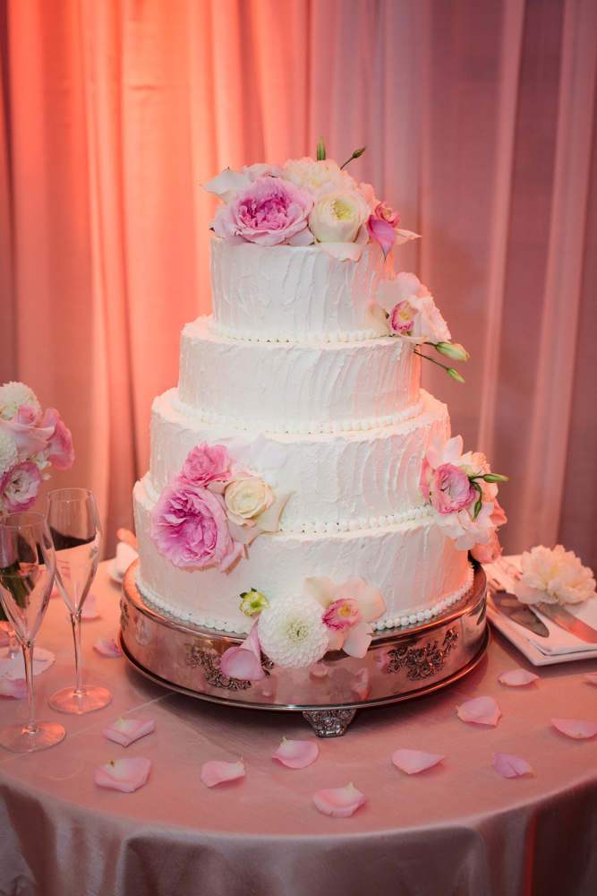 4-tiered white wedding cake with blush and white floral accents
