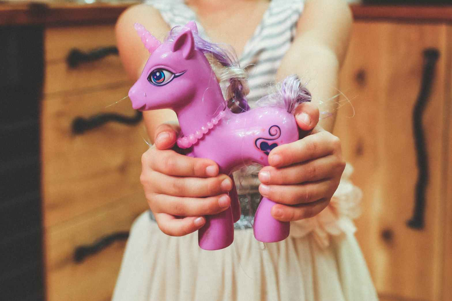 Young girl holding toy pony with both hands in front of camera. The pony has a plastic necklace, a unicorn horn, & tangled hair coming from it's mane, and has a tattoo of a heart on it's side. Moxie Family Therapy offers therapy for children, play therapy in orange county, art therapy for children, and more. Contact our child therapist today for the support you deserve!