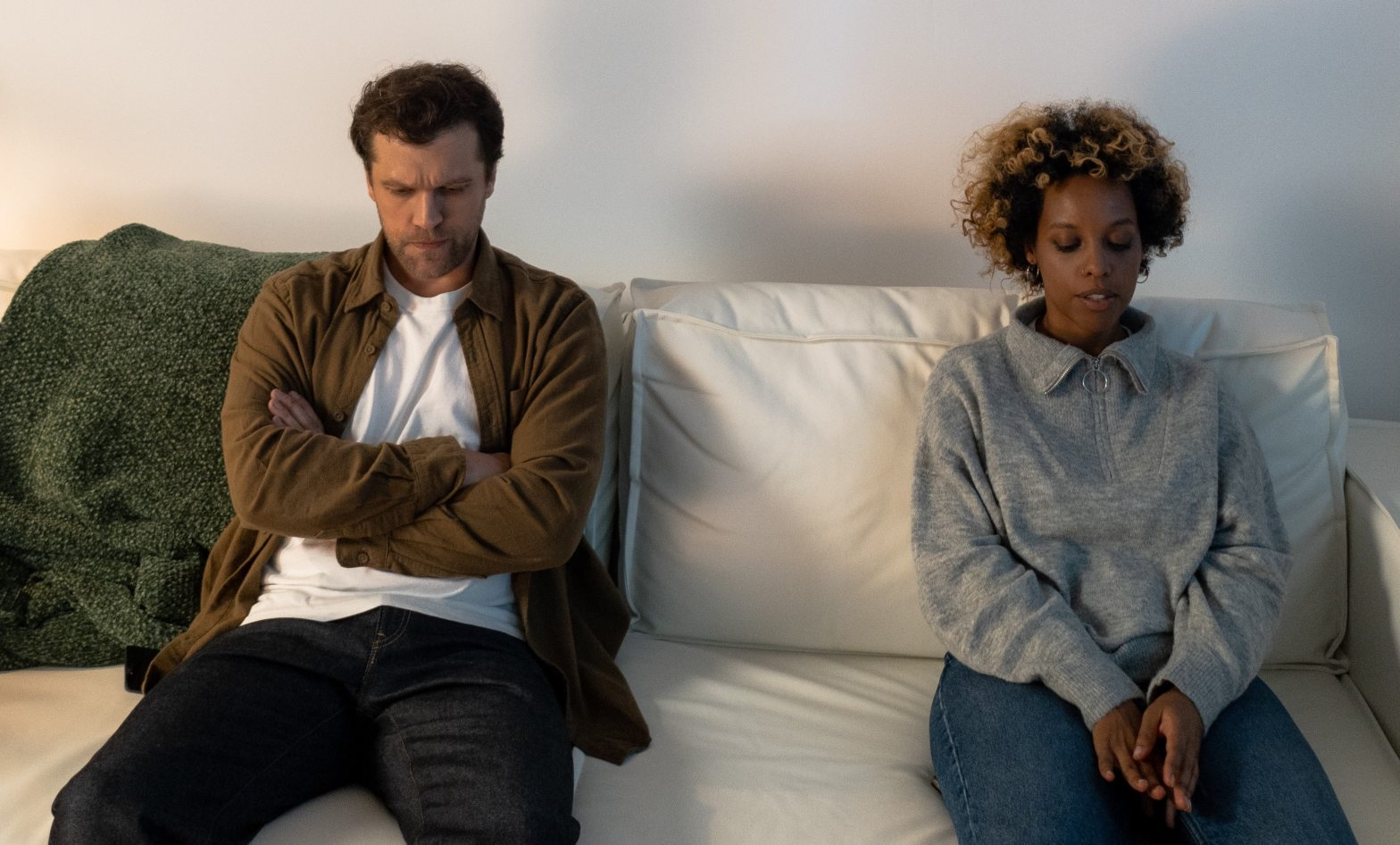 An couple sits on either side of a sofa as they avoid each others eyes. They're relationship has been through a lot, and they are seeking marriage counseling in Orange County, CA. Moxie Family Therapy offers couples therapy and marriage counseling in Orange County, CA, relationship counseling, online couples therapy, and more.
