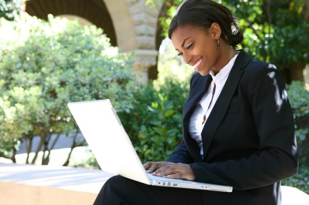 African American businesswoman smiles as she types on her laptop outside. She is looking up options for online therapy in orange county, ca. Moxie Family Therapy offers online therapy in california, online trauma therapy in orange county, ca, and more.
