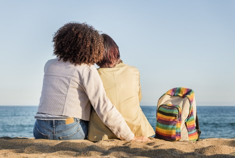 A lesbian couple embrace in front of the sea next to a rainbow-colored backpack. This symbolizes the connection and closeness that comes after opening up to an LGBTQ therapist. We offer LGBTQ therapy in Orange County, CA, gender therapy, and more. Contact a transgender therapist today for support!