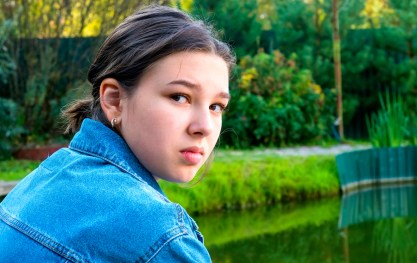 A teenage girl looks over her shoulder at the camera with a serious expression. This could symbolize a teen withdrawing from family. A therapist for teens in Orange County, CA can support your with teen family therapy, therapy for teens, and more.