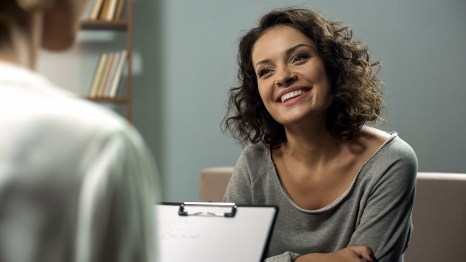 Smiling woman sits as she listens to the therapist across from them. They are talking about the best options for addressing her trauma symptoms. Moxie Family Therapy offers trauma therapy in Santa Ana, CA, Orange County trauma treatment, and more. Contact a trauma therapist for the support you deserve.