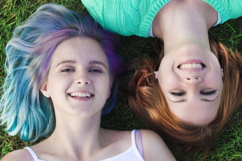 A top down perspective of two cheerful lesbian girls lay on the grass in the park. They appear close, and are happy to be next to one another. This could symbolize the loving feelings of being part of a community. We offer support for LGBTQIA+ folx, and counseling for women in Orange County, CA. Contact an LGBTQ therapist for LGBTQ therapy today!