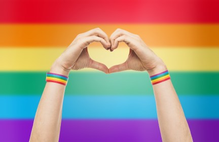 Close up of hands with rainbow wristbands making a heart gesture in front of a rainbow background. This could symbolize the support one might feel after meeting with an LGBTQ therapist in Santa Ana, CA. Contact Moxie Family Therapy for online LGBTQ therapy in California, counseling for women in Orange County, CA, and other services.