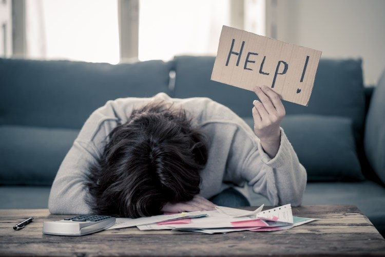 """A woman lays with her head on a table while holding a sign that reads """"Help!"""" This could represent feeling drained from empathy fatigue in California. Learn about therapy for therapists in Orange County, CA, and compassion fatigue treatment can help you today!"""
