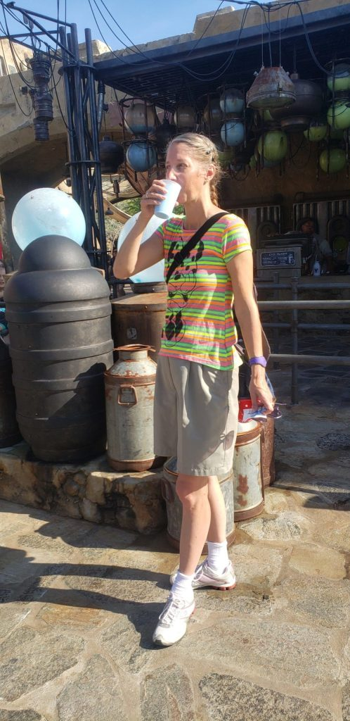 Trying blue milk in front of the Milkstand at Star Wars Galaxy's Edge in Hollywood Studios Disneyworld