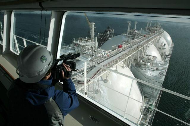 A cameraman films an LNG tanker in a 2009 file photo. (Photo credit NATALIA KOLESNIKOVA-AFP-Getty Images)