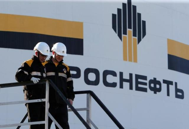 Workers stand next to logo of Russia's Rosneft oil company at central processing facility of Rosneft-owned Priobskoye oil field outside Nefteyugansk