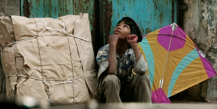 Image still from the film Patang, of a boy sitting with his kite and looking to the sky.
