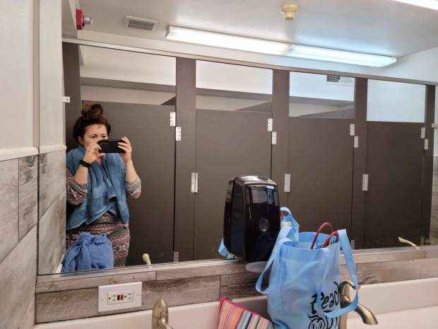 Yvonne taking a bathroom selfie with a blue towel around her shoulders and hair in a bun. The selfie shows the mirrors, stalls, and some of the sinks.
