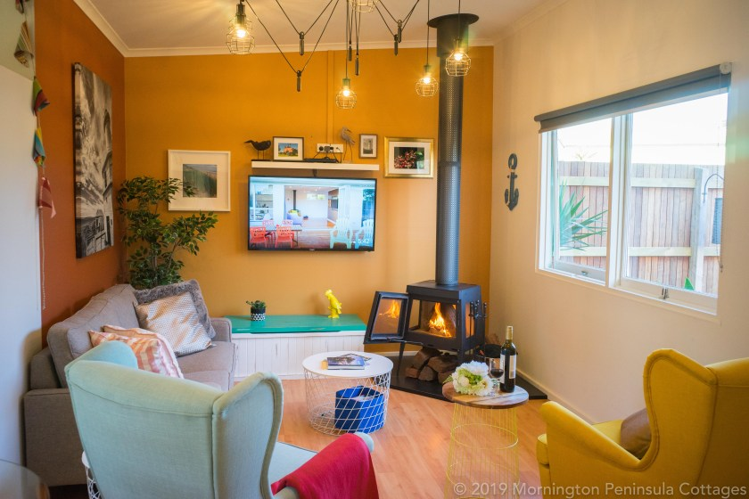 The living room of the Beach Club cottage with new wood fireplace and TV