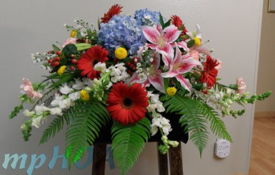 # MPCASK0011 — $275.00 — Blue Hydrangeas, Pink Oriental Lilies, Red Gerberas, White Snap Dragons, Pink Carnations, Red Hypericum, White Monte Casinos, Yellow Button Pom Poms. ~ Approximate size: 18″H x 36″W