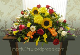 # MPCASK009 — $250.00 Yellow Mini Calla Lilies, Yellow Roses, Sun Flowers, White Roses, White Gerberas Daisies, White Daisie Pom Poms, Orange Gladiolous, Pink Purple Gladiolous, Yellow Pom Poms. ~ Approximate size: 18″H x 36″W.