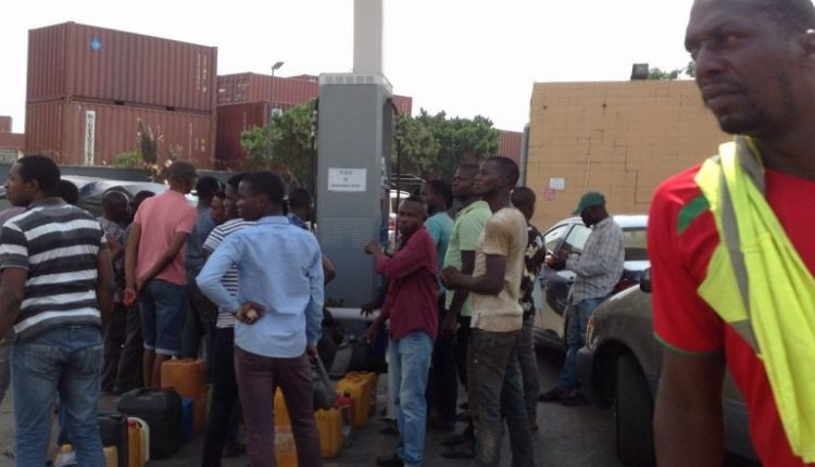 People queue up with their fuel keg at Mobil filling station