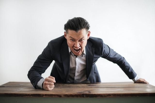 一位情緒激動的男生用手敲桌子