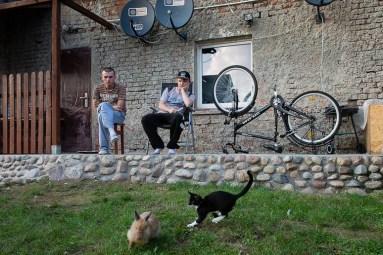 Broniszow, 12.09. 2015. Bracia przed domem ogladaja harce krolika z kotem. Fot. Joanna Mrowka / FORUM