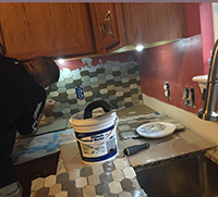Tiles being placed onto a wall for a kitchen backsplash DIY