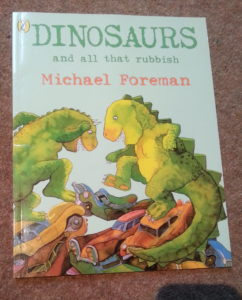 Front cover shows two green dinosaurs happily jumping on a pile of cars