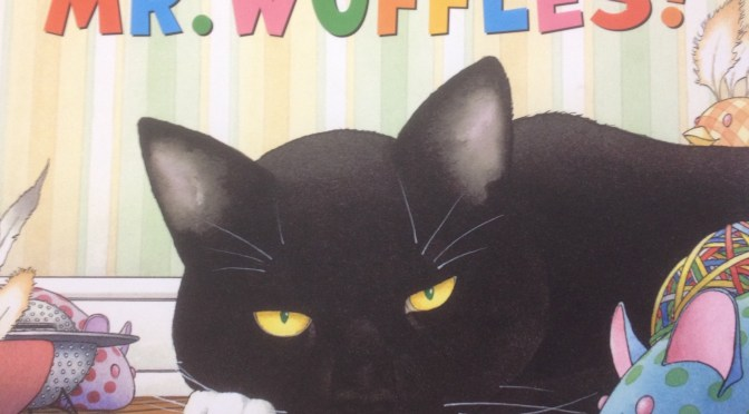 Front cover of Mr Wuffles showing a grumpy looking black cat with white paws lying down on a wooden floor