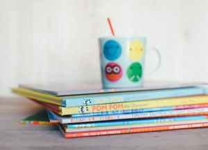 A stack of picture books with a mug on top