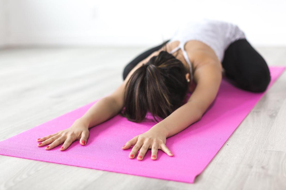 woman doing yoga pose on pink yoga mat