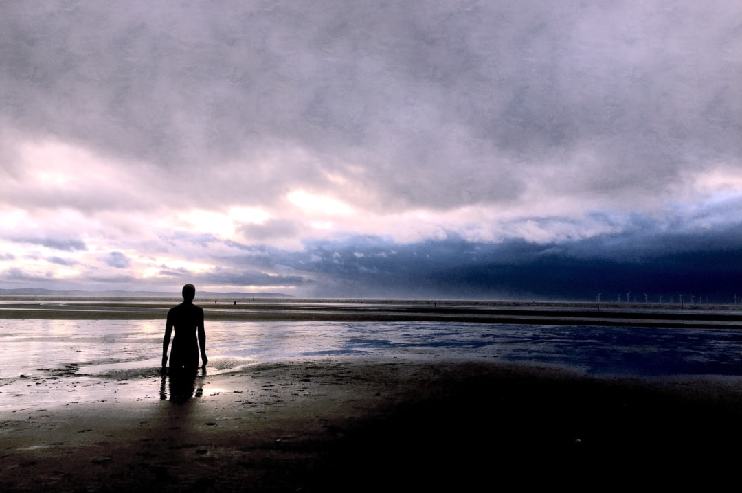 A photograph of a solitary statue by Antony Gormley on Crosby Beach - Robin Williams, Suicide & Me - Mrs H's favourite things