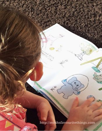 A little girl reading a copy of the Parragon Book A Collection of Nursery Rhymes