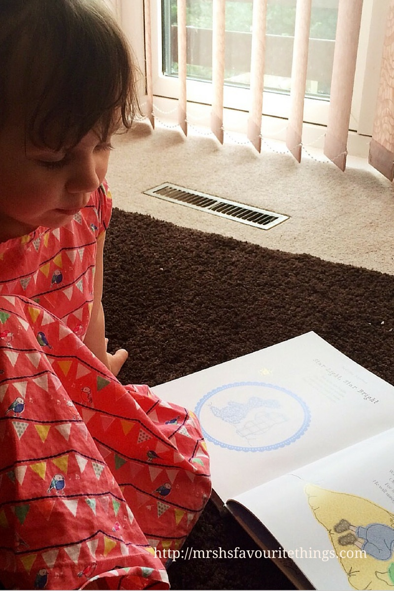 A little girl in a red dress sitting on the floor in front of a window reading the Parragon Book A Collection of Nursery Rhymes_Mrs H's favourite things