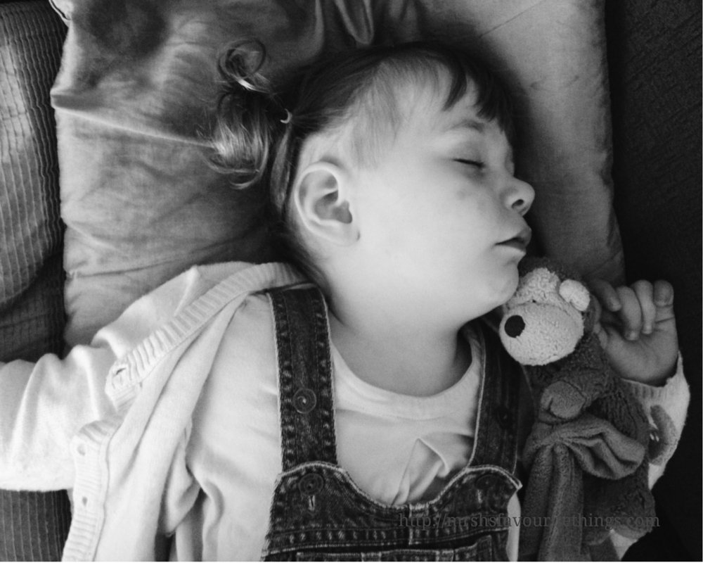 A black and white picture of a little girl with bunches in her hair and wearing dungarees, lying asleep on the sofa hugging a toy monkey_ An A to Z of Little Miss H _ Mrs H's favourite things