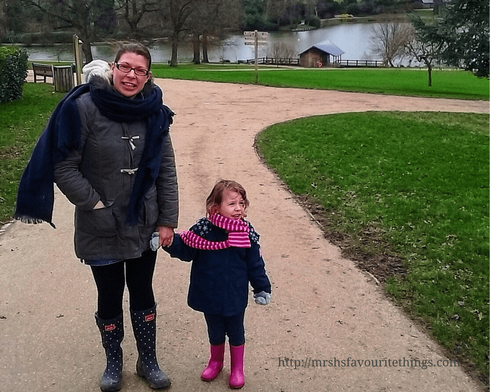 A lady holding hands with her daughter who are dressed up in warm weather gear and standing in a park in front of a lake_Days out in the winter sunshine - My Captured Moment_Mrs H's favourite things