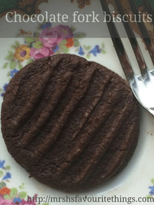 "A chocolate biscuit on a pretty floral plate with the prongs of a fork in sight_ with the title ""chocolate fork biscuits""_chocolate fork biscuits_Mrs H's favourite things"