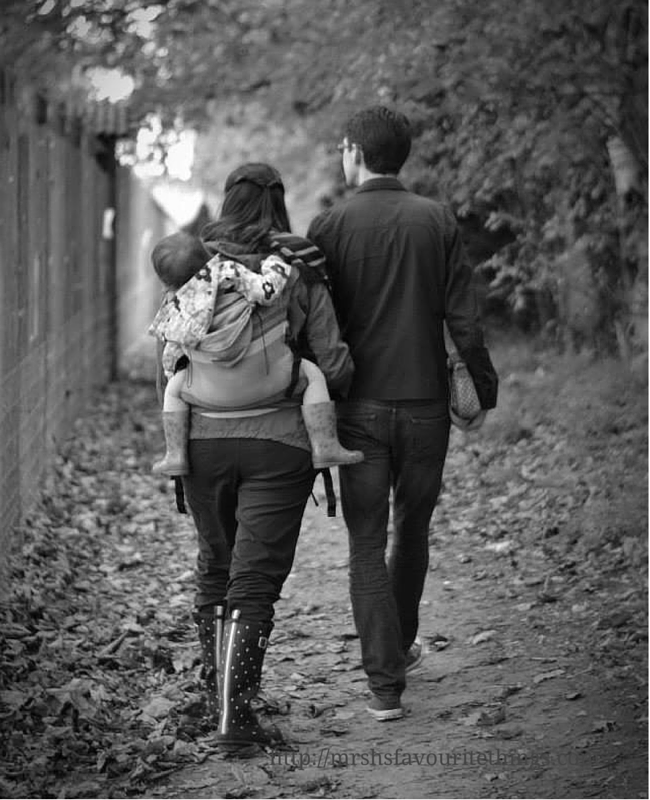 A black and white photo of a man and his wife and his daughter walking away from the camera_ the wife is baby wearing her toddler daughter on her back in a Lenny Lamb toddler ergo carrier in Caffe Latte Lace__baby wearing love_Mrs H's favourite things