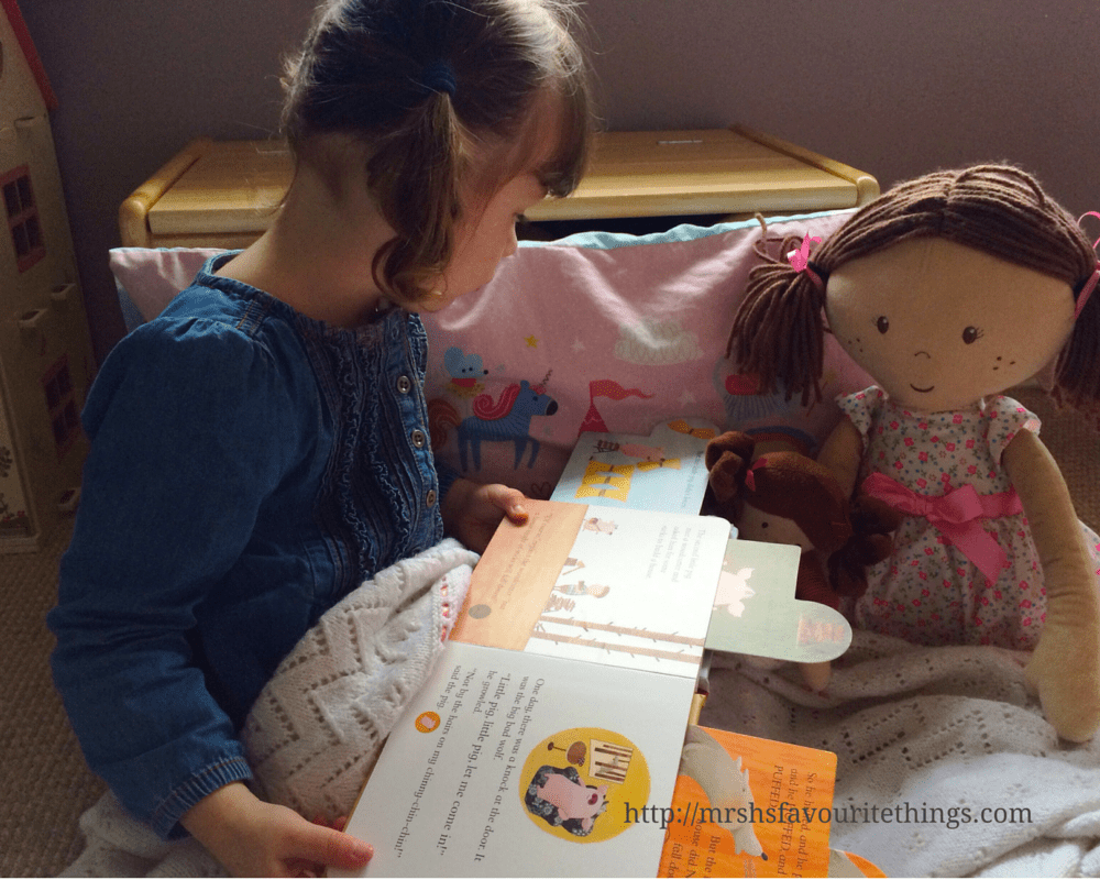 A little girl with bunches and wearing a denim dress sits with her two rag dolls and reads to them from Three Little Pigs, a Parragon Book - Three Little Pigs_A Parragon Book Review_Mrs H's favourite things