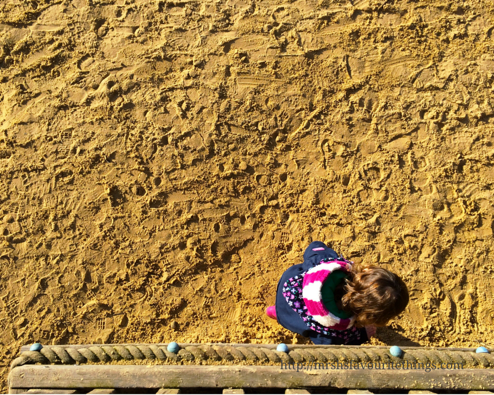 A photograph from above of a little girl with brown curly hair wearing a navy coat and a pink and white stripey fleece walks across a sand pit at a play park_Because I'm happy_December 2015 and January 2016_Mrs H's favourite things
