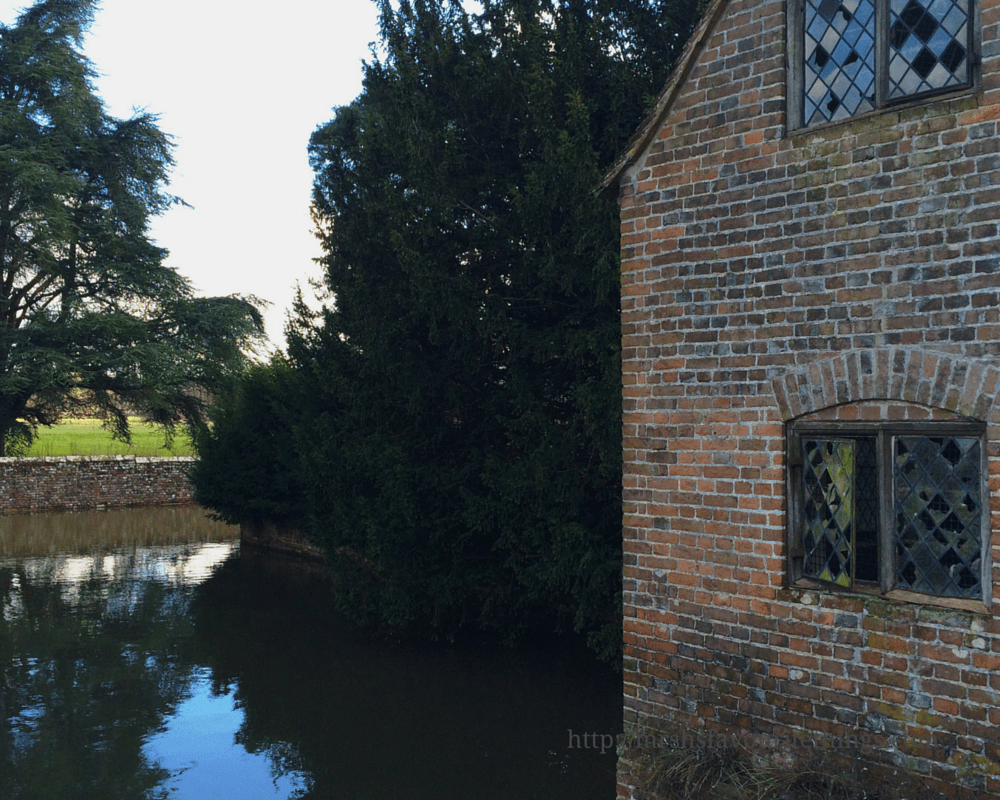A photograph of a moat surrounded by a brick wall and trees with a brick boat house with diamond windows at Groombridge Place _ A perfect Mother's Day _ Mrs H's favourite things