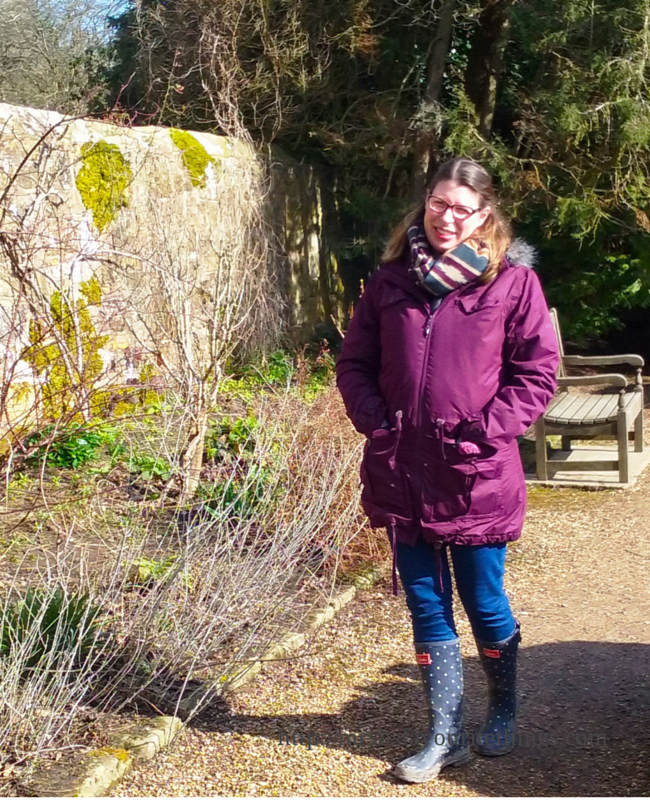 A young woman stands in the grounds of a stately home, she is wearing polka dot wellies, jeans, a purple waterproof coat from Trespass and a patterned scarf _ Finding the perfect coat with Trespass _ Mrs H's favourite things
