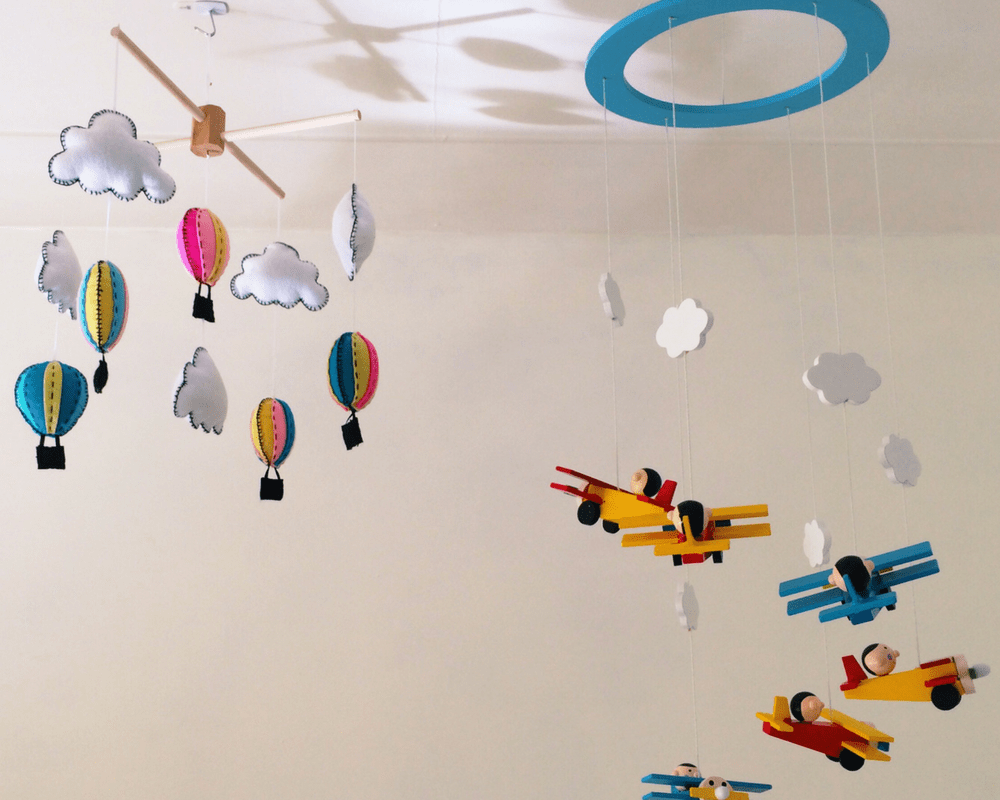 A photograph of two mobiles hanging in a nursery - one is made of felt and is hot air balloons and clouds - the other is wooden and features aeroplanes in bright primary colours - Little Mister H's rainbow themed nursery - a tour and a vlog - Mrs H's favourite things