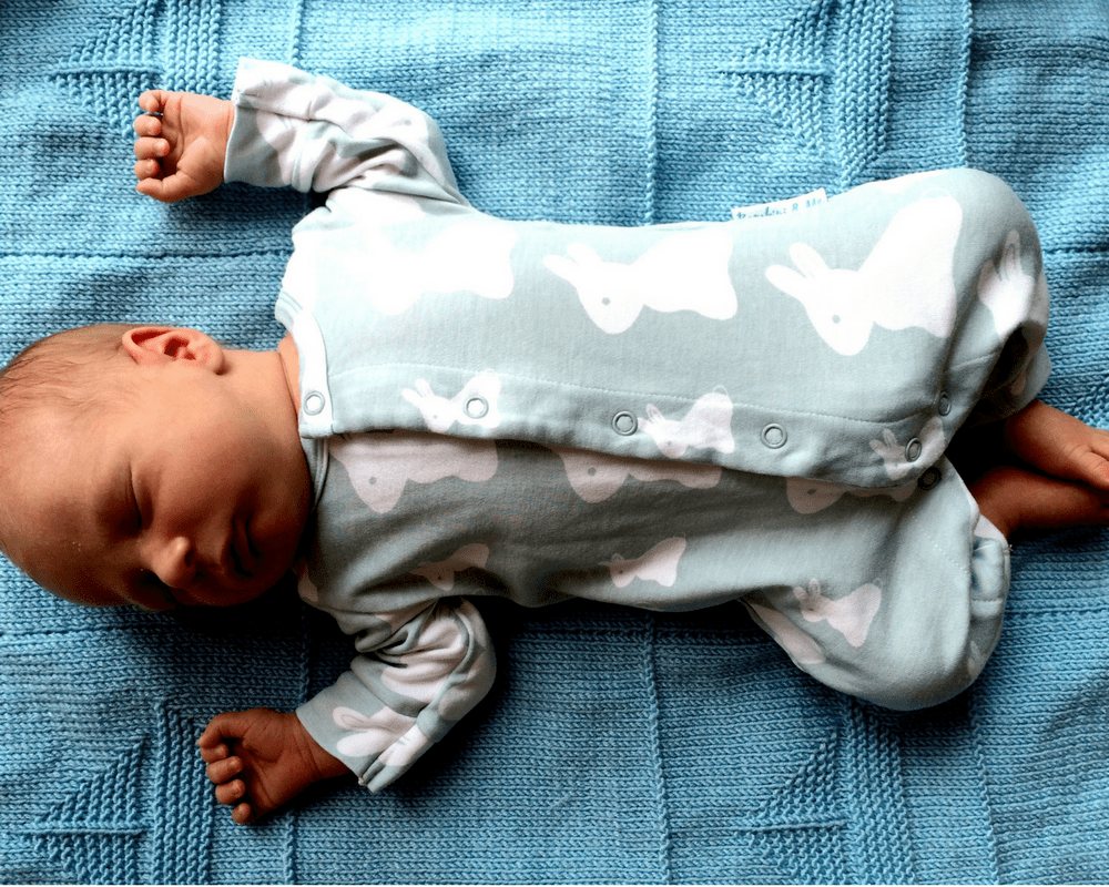 New born baby boy lying on a blue knitted blanket wearing a gorgeous crystal blue bamboo bunny romper suit from the company Bambini & Me _ Mrs H's 10 favourite things - May/ June/ July 2016