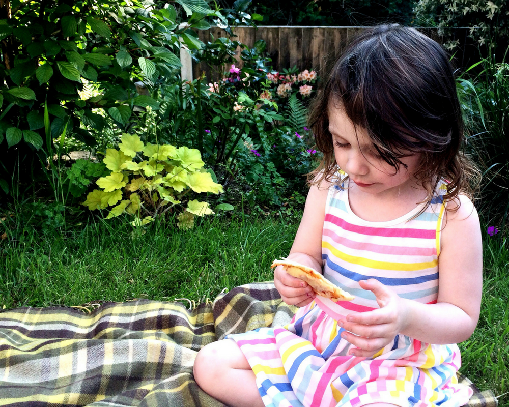 A gorgeous little girl with brown curly hair sits in her garden having a picnic tea wearing a rainbow coloured and white striped dress from H&M_ Mrs H's 10 favourite things - May/ June/ July 2016 - Mrs H's favourite things