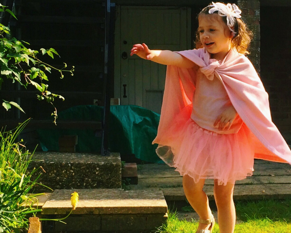 A little girl dressed in pink with bunches and a hairband stands in a garden and smiles_Super Skye, the superhero - #Vertbaudetheroes - Mrs H's favourite things
