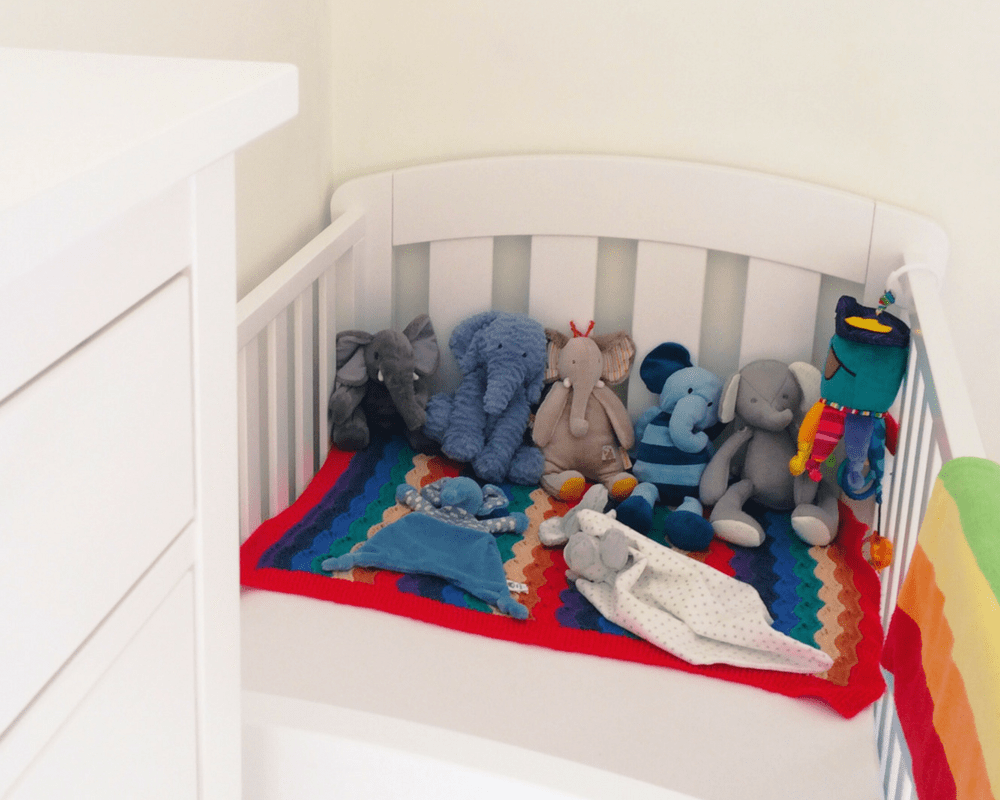 A photograph of a white cot bed - the Sunshine cot bed from the Urbane collection by Boori - covered in a white sheet and accessorised with two rainbow blankets and a number of colourful elephant toys - Little Mister H's rainbow themed nursery - A tour and a vlog - Mrs H's favourite things